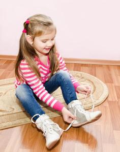 cute-little-girl-tying-her-white-shoes-home-36213353